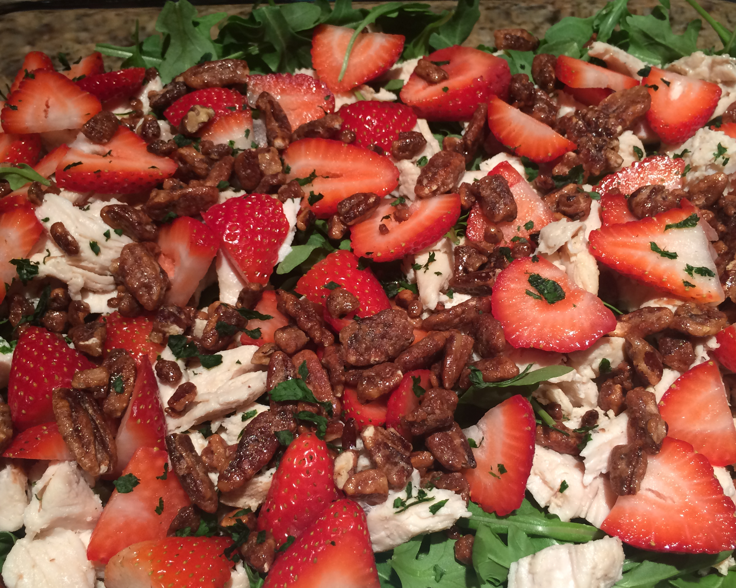 Arugula salad with grilled chicken, strawberries, candied pecans and goat cheese